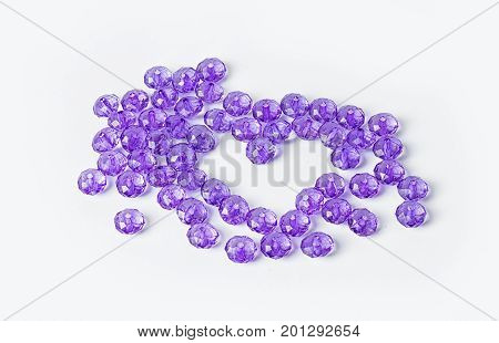 acrylic beads on a white background. Acrylic beads for design. Heart of purple beads on a violet background