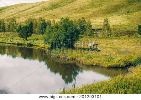 Abandoned summer alcove near beautiful pond with calm water next to meadow with native grasses trees and hills in distance; Altai mountains Russia Aya district