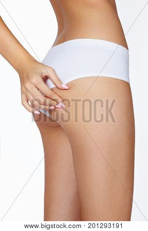 The woman squeezes a skin on a hip for check on a cellulitis
