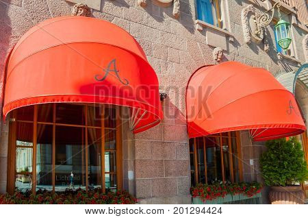 ST PETERSBURG RUSSIA - AUGUST 15 2017. Red awnings of Famous Astoria hotel at Bolshaya Morskaya street in St Petersburg Russia in sunny day -closeup facade street view of St Petersburg Russia architecture details