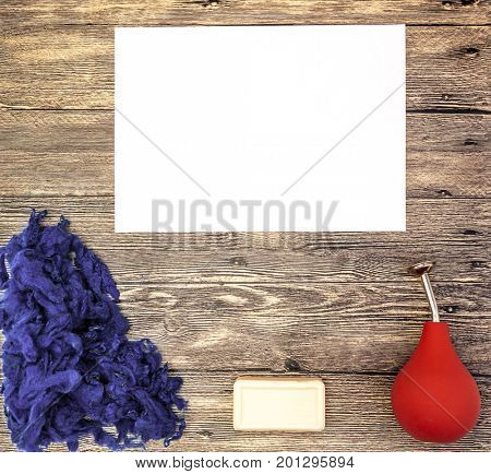 Felting or knitting mockup place for text, with blue wool, soap, orange watering felting on a wooden background.