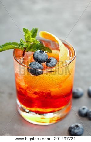 Closeup Glass Of Iced  Berry Soda, With Fruit Syrup Topped With Sliced Fresh Orange And Blueberry On