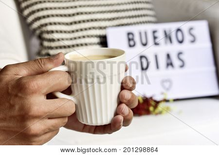 closeup of a young man with a white ceramic cup with coffee in his hand and a lightbox in the background with the text buenos dias, good morning in Spanish written in it