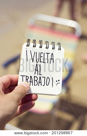 closeup of a young man in the beach showing a spiral notepad with the text vuelta al trabajo, back to work in Spanish in front of a deck chair in the seashore