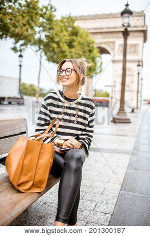 Lifestyle portrait of a young stylish business woman sitting outdoors near the famous triumphal arch in Paris