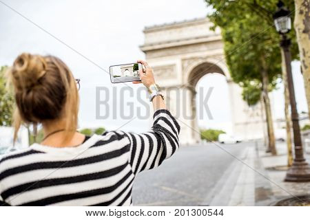 Young woman tourist photographing with phone famous triumphal arch in Paris