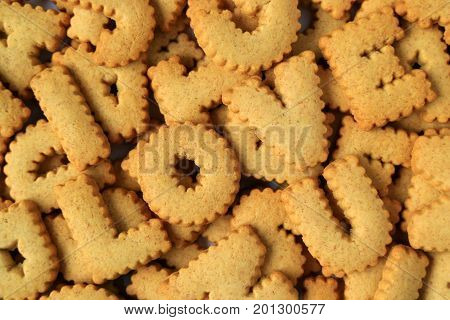 Top view of the word I LOVE YOU spelled with alphabet shaped biscuits on the pile of of the same biscuits