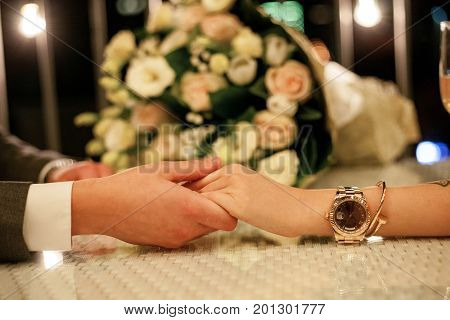 Man makes woman marriage proposal at table in restaurant and holding her hand. There is bouquet of roses in background.
