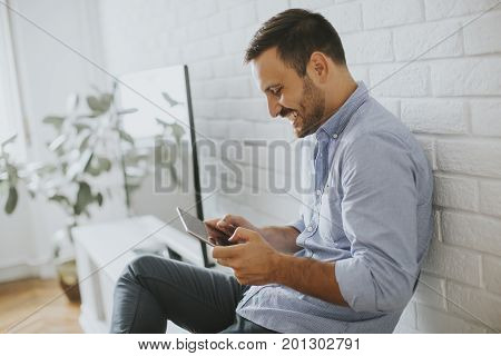 Happy Man Browsing In A Tablet Sitting On Commode At Home