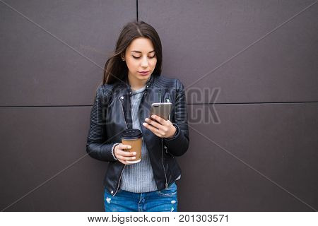 Joyful Young Woman Texting And Holding Coffee While Leaning Against Wall In Urban Outside