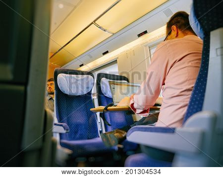 MUNICH GERMANY - AUG 8 2017: German worker insidefast ICE train commuting worker on laptop for the next important project - commuting home going to work