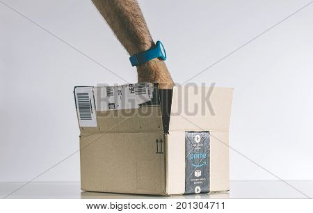 PARIS FRANCE - JUL 30 2017: Male hand searching for product inside the open Amazon Prime logotype printed on cardboard box side. Amazon is an American electronic e-commerce company distribution worlwide e-commerce goods