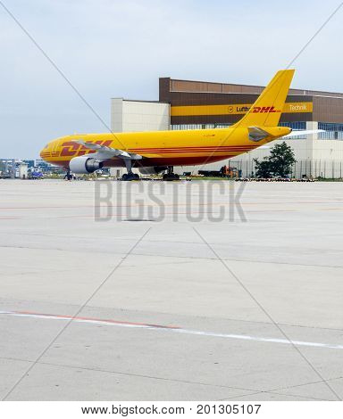FRANKFURT GERMANY - AUG 8 2017: Yellow Airbus A300-600 serving DHL parcel delivery company loading and unloading parcels for delivery on time a the Frankfurt Airport Cargo zone