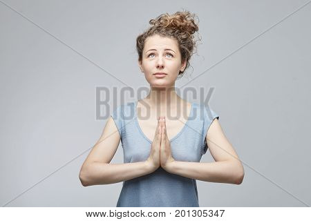 Headshot of young European student female in casual clothes begging for good luck at exam. Pretty woman with curly curvy hair asking for help having hopes for good. Hopeful emotional woman praying.