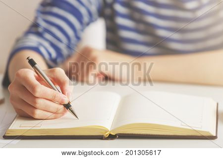 Woman Writing In Hardcover Notepad