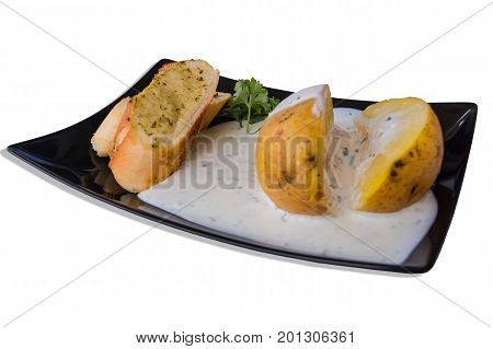 Pell potatoes with herb quark and baguette on a black plate