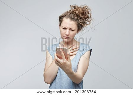 Tragic emotions feelings facial expressions concept. Woman looking at the screen of her modern mobile phone with regardful look after learning unpleasant news while checking e-mail on her gadget .
