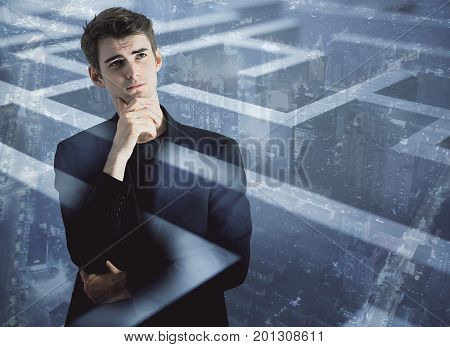 Thoughtful young businessman on abstract city background with maze labyrinth. Challenge concept. Double exposure