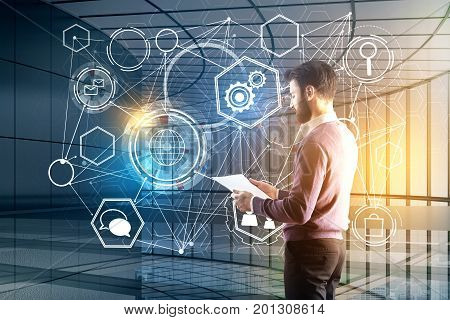 Handsome young european businessman with laptop and digital business screen on blurry office interior background. Technology and analytics concept. Double exposure