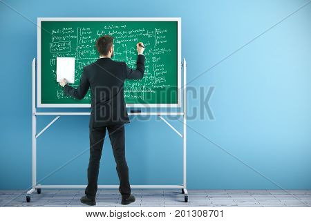 Back view of businessman writing mathematical formulas on chalkboard placed in interior with blue wall and wooden floor. Learning concept. 3D Rendering