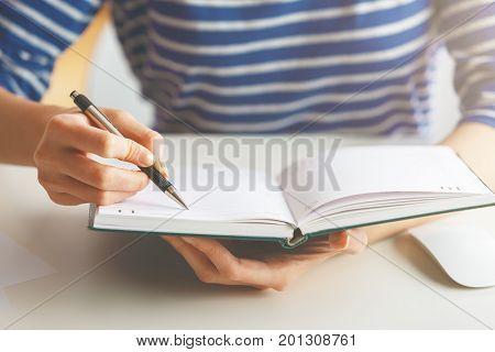 Woman Writing In Hardcover Diary
