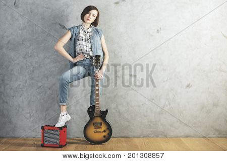 Caucasian woman with electric sunburst guitar and amplifier standing in studio room with wooden floor and concrete wall. Musician concert hobby leisure rehearsal concept