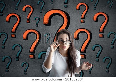 Surprised young european woman on brick wall background with drawn question marks. Curiosity concept