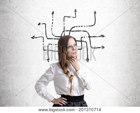 Portrait of a pensive young businesswoman with braided hair standing near a concrete wall with an arrow labyrinth on it.