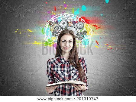 Portrait of a smiling beautiful teenage girl in a checkered shirt holding an open book and standing near a blackboard with a colorful brain sketch and gears on top of it
