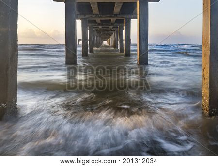sunrise image of the view under the ocean pier along the Gulf of Mexico in Port Aransas Texas