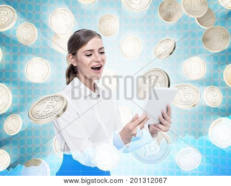 Portrait of a happy woman looking at her tablet computer and standing under a bitcoin rain against a futuristic background. Toned image double exposure