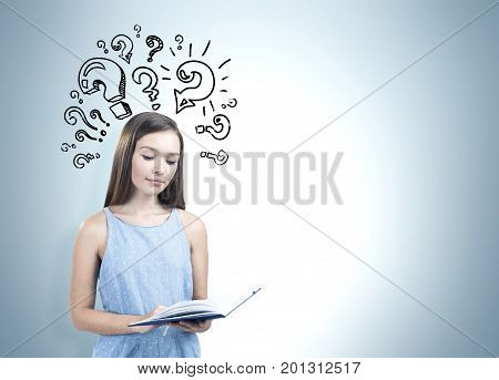 Portrait of a teen girl wearing a blue dress and holding an open book. She is reading while standing near a gray wall with question marks on it. Mock up
