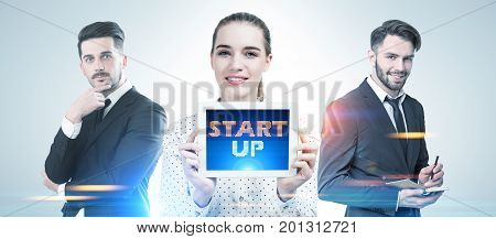 Three business partners two men and a woman are standing together and portraying success in a morning city. A woman is holding a tablet computer with a start up text. Toned image double exposure