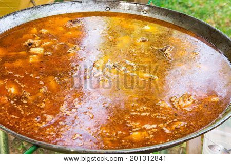 Process of cooking Spanish Valencian paella or jambalaya in large flat frying pan. Ingredients meat rice vegetables spices simmering in broth with tomato sauce.Outdoors picnic lifestyle