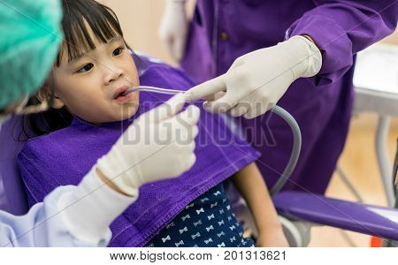 Dentist And Assistant Checking And Cleaning Asian Girls Teeth Using Suction Machine In The Dentists