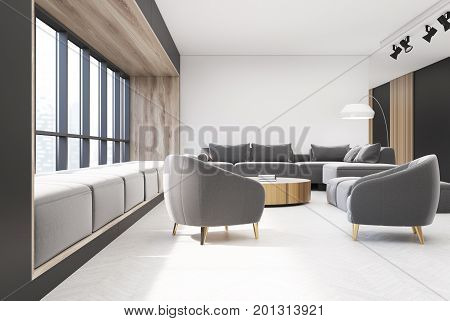White and wooden living room with a wooden floor a round narrow table and gray sofas and armchairs. There is a panoramic window with soft cushions on the window sill. 3d rendering mock up