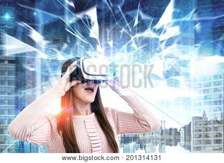 Close up portrait of a young woman wearing a pink cardigan and VR glasses. She is amazed by what she is seeing. She is standing against a night city background. Polygons. Toned image double exposure