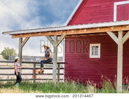 horizontal image of two caucasian women dressed in cowgirl outfits perched on a wooden fence having a conversation by a red barn in the summer time.