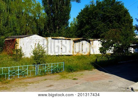 Old abandoned garages near houses. Dead radioactive zone. Consequences of the Chernobyl nuclear disaster August 2017
