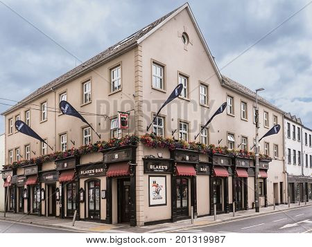 Galway Ireland - August 3 2017: Historic Blakes Bar and guesthouse two facades on corner with street view. Flowers flags awnings and signs.