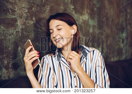 Young woman listen music with headphones and relaxing. Sitting on cafe domestic atmosphere. Positive emotionclosed eyes loft interior