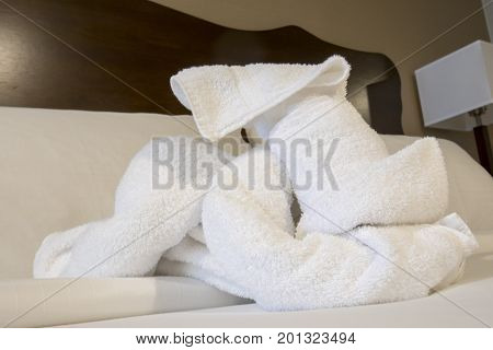 Folded terry cloth towels in shape of dog on hotel bed.