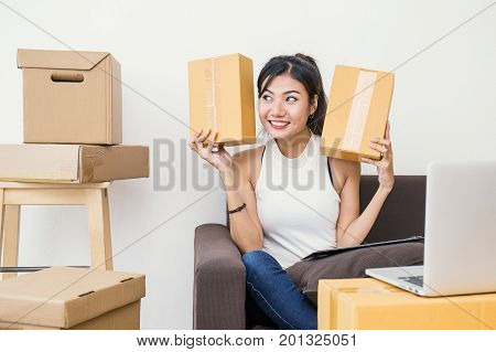 Start up small business entrepreneur SME or freelance woman holding boxes working at home concept Young Asian small business owner  SME at home office online marketing packaging box and delivery