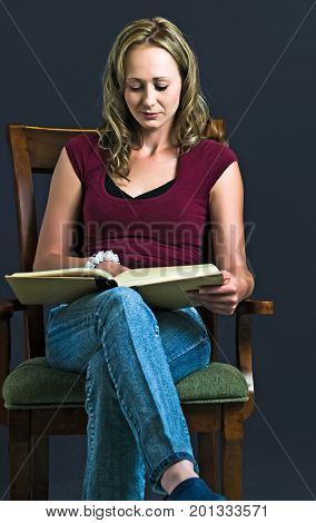 Pretty young lady seated in an arm chair reading a research book.