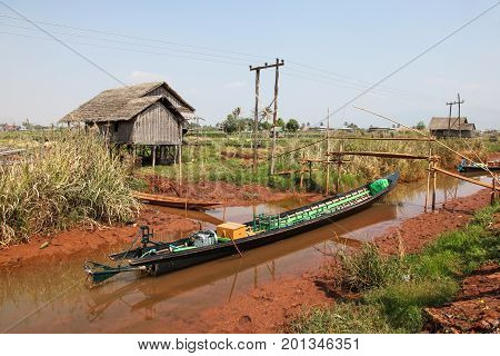 Rural scene at Inle Lake Myanmar - Burma. A long tail boat in one of the canals that leads to Inle Lake. Inle lake is Myanmar's second larget lake and a popular tourist destination.Traditional style long tail boats like this are used on the lake.