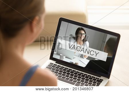 Young unemployed jobless woman looking for job, browsing web services searching work, reviewing available vacancies to submit resume and apply, close up view over the shoulder, focus on laptop screen