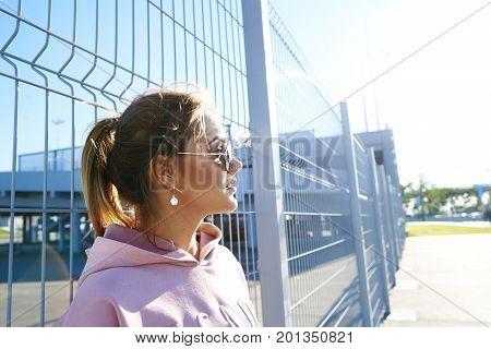Modern lifestyle summer and city life. Profile of stunning cute teenage girl in trendy shades wearing her blonde hair in ponytail enjoying sunny day leaning back on netting in urban surroundings