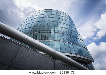 LONDON ENGLAND - JUNE 17 2016: Upward picture of one of the buildings belonging to London Bridge City in a sunny day with clouds and a handrail crossing the lower part of the building. London.