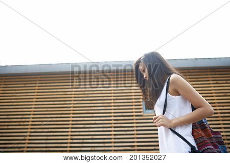 Outdoor lifestyle portrait of beautiful young brunette Asian woman wearing white dress and backpack walking by wooden construction looking down spending summer vacations in tropical country