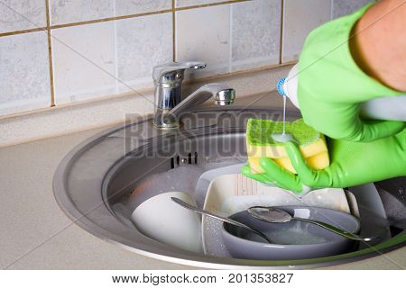 Sink full of washing dishes filled with dish soap water and hands in green gloves.